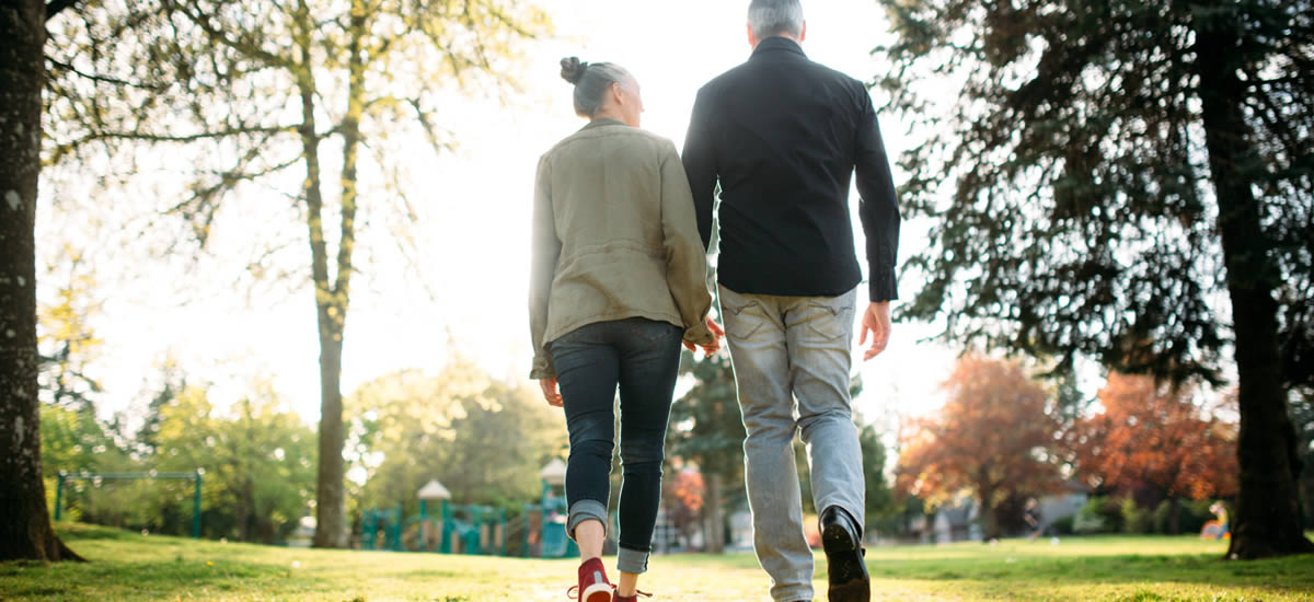 A couple holding hands walking in the park